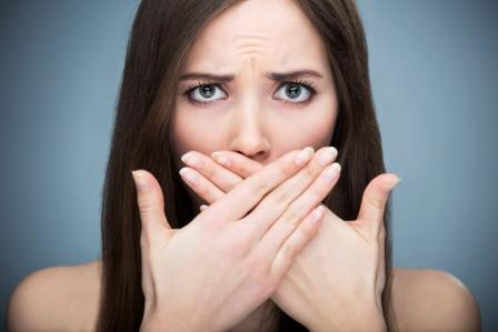 A women covers her mouth due to gum disease.