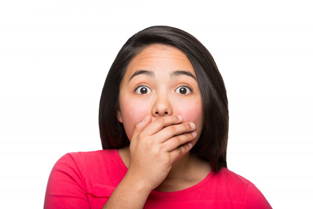 A girl covering her mouth because of her embarassing gum disease. If you have gum disease visit Arizona Periodontal Group to have your gum disease treated.