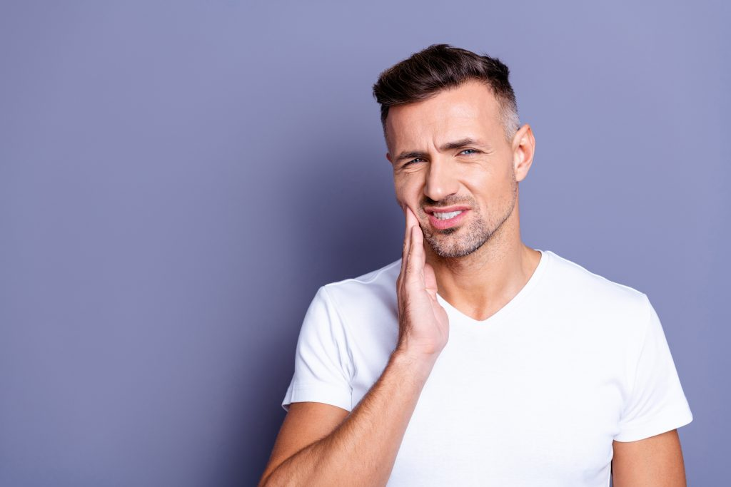 Man has jaw pain caused by malocclusion and is holding his cheek.