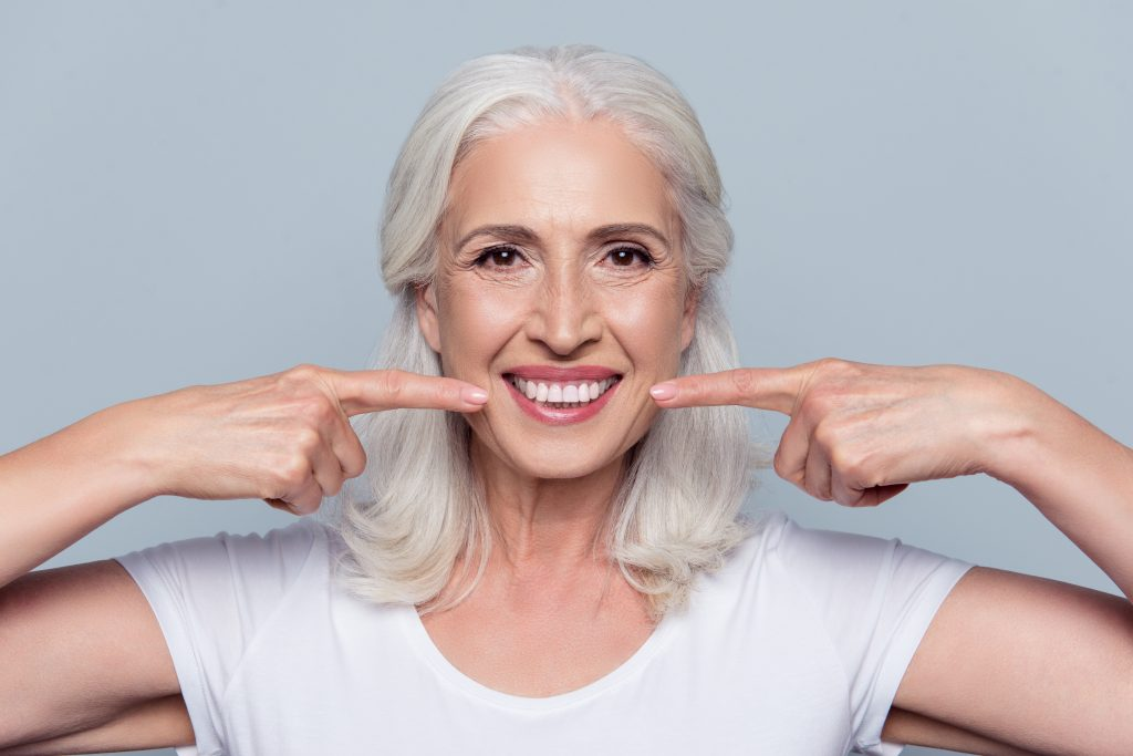 Woman with dental implants smile isolated on gray background