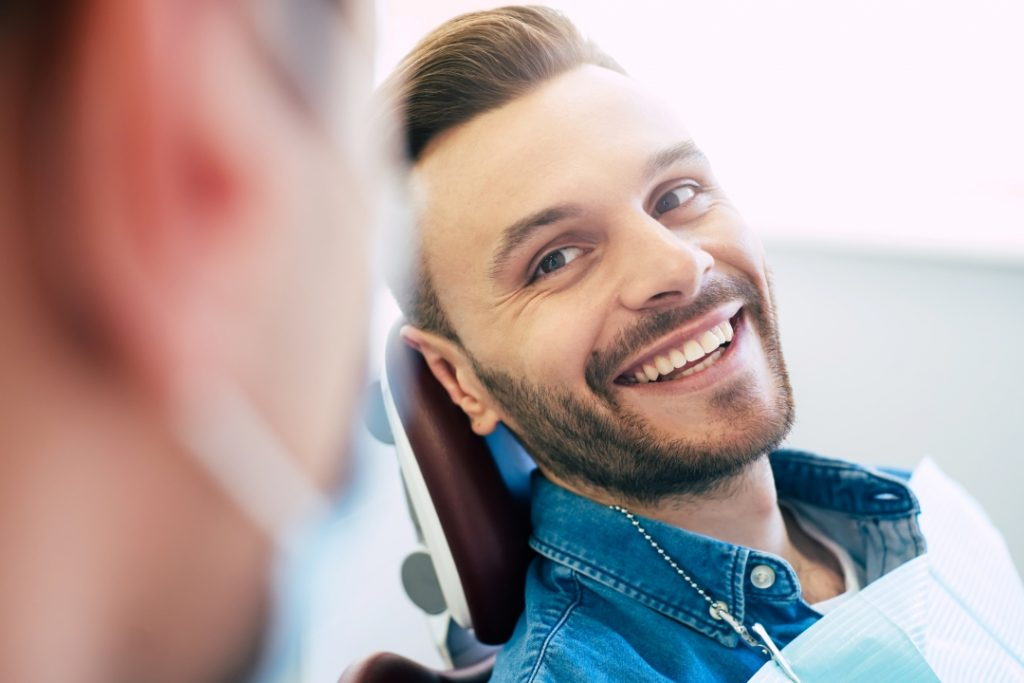 Man in a dental chair smiling at the periodontist