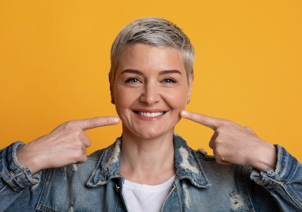 Woman smiling and pointing to her dental implants