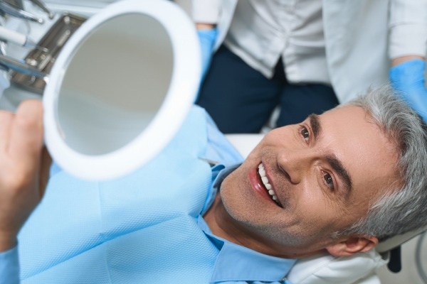 man smiling after getting dental implants - Arizona Periodontal Group