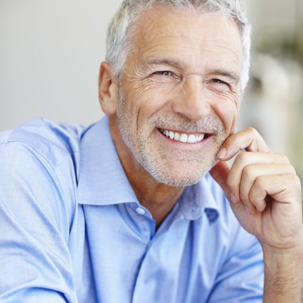 a man smiling outside with realistic dental implants