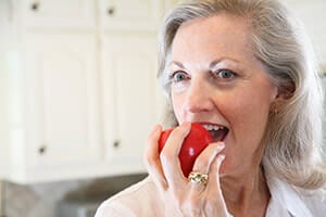 Woman eating an apple after getting dental implants from Arizona Periodontal Group